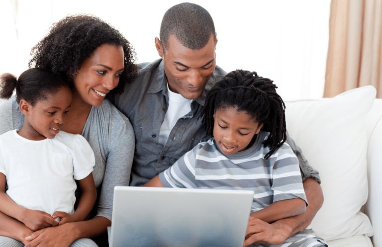 Image of family gathered around laptop