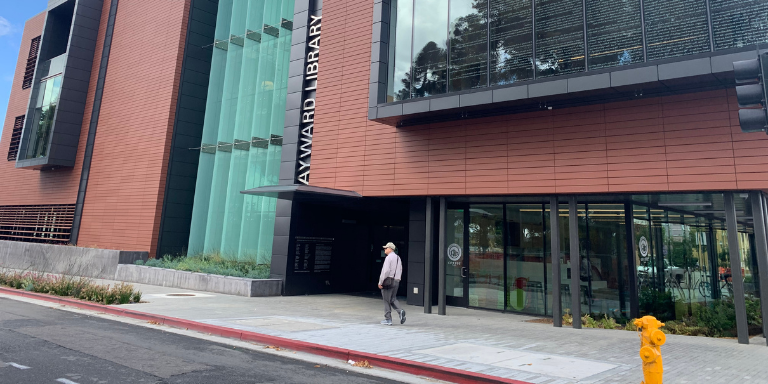 A person walking in front of the Downtown Hayward Library