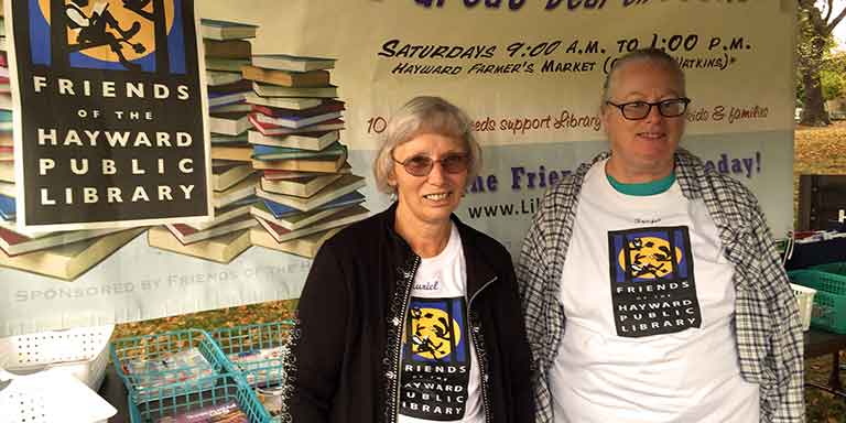 Two women standing in front of a Friends of the Hayward Library book sale