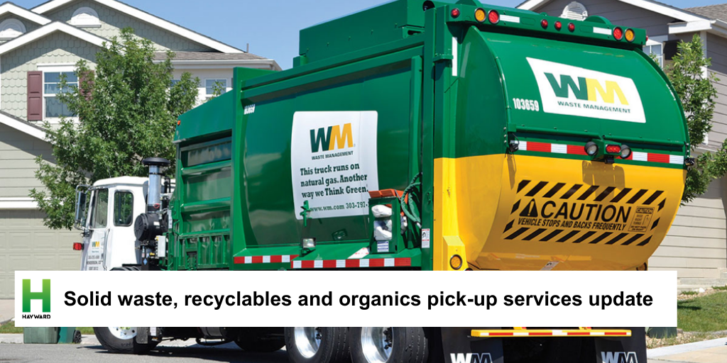 Waste management truck picking up trash cans
