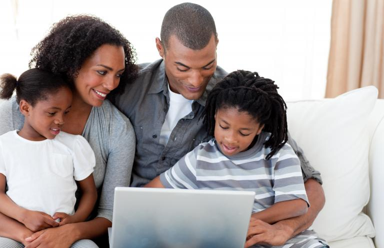 Image of family gathered around laptop