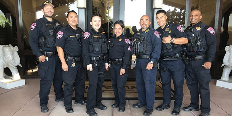 Police officers smiling and standing in front of a building