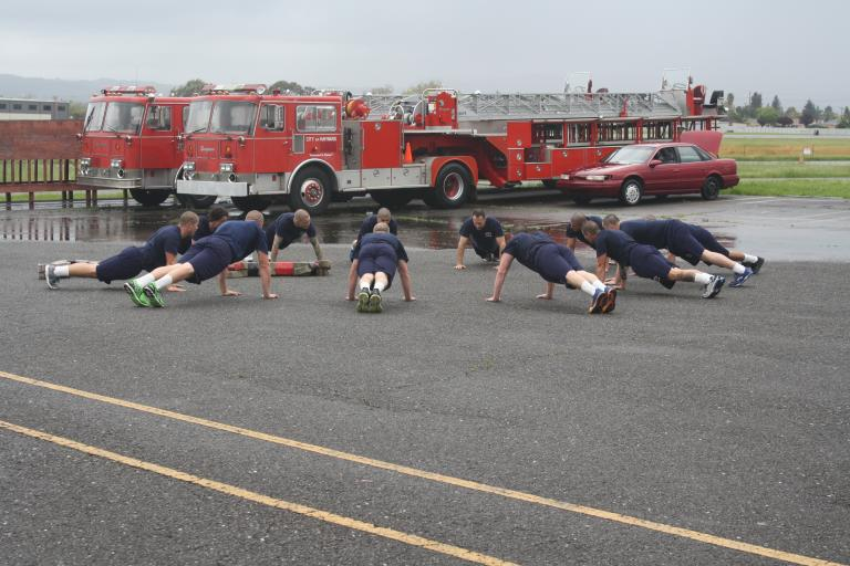Hayward Fire Department recruits plank in front of two fire engines