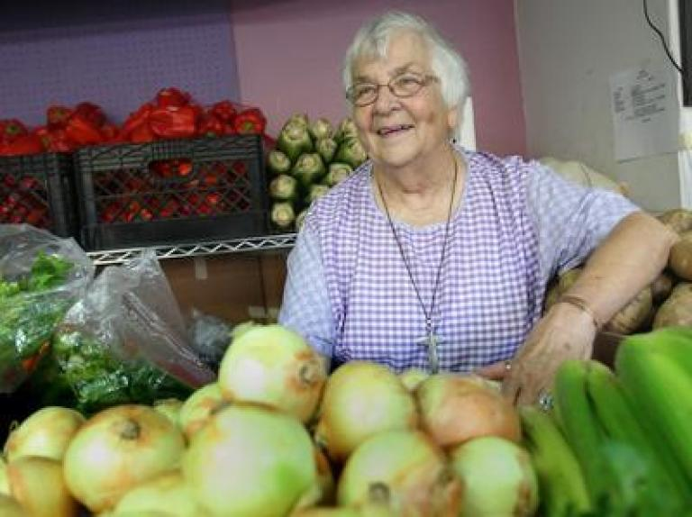Betty Deforest wearing a purple shirt standing in a room with boxes of fresh food