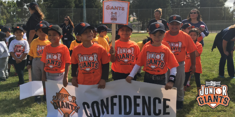 A group of smiling children wearing black and orange San Francisco Giants baseball hats and Junior Giants tee shirts holding a white sign that says confidence