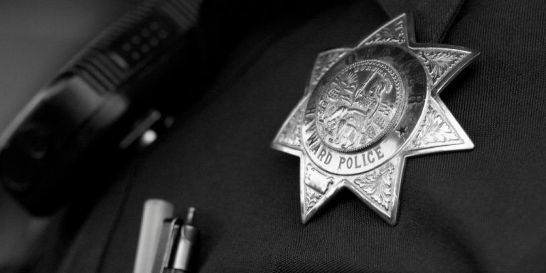 A black and white close up of a police badge