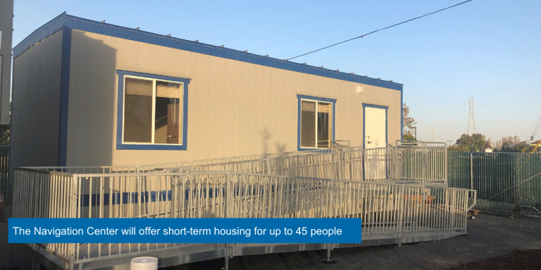 A blue and grey portable building with a wheelchair ramp