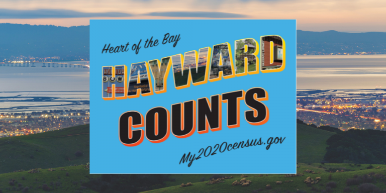 A blue Hayward Counts 2020 Census Sign on top of an image of the Hayward Skyline