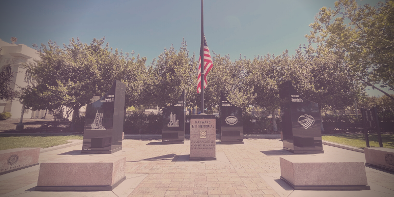 Photo of the Hayward 9/11 Memorial, a paved space with four large black rectangular structures with engravings. In the center, a brown rectangular block with the US flag rising from it.