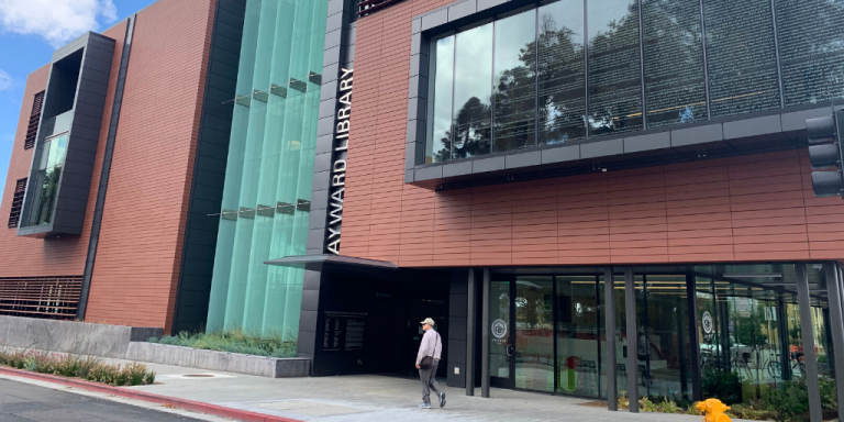 Image of a person walking in front of the Hayward Library, a large, dark red building with glass doors and windows throughout.