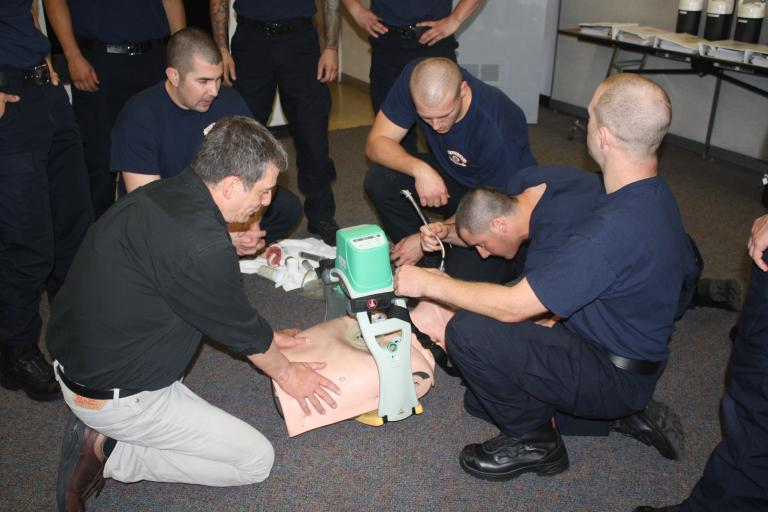 Fire fighter recruits practicing how to intubate patients in a classroom