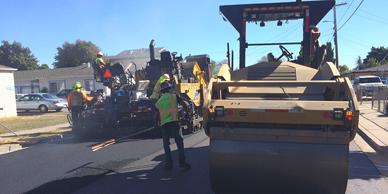 People in safety vests working on repaving the left side of a road with large pavement equipment.
