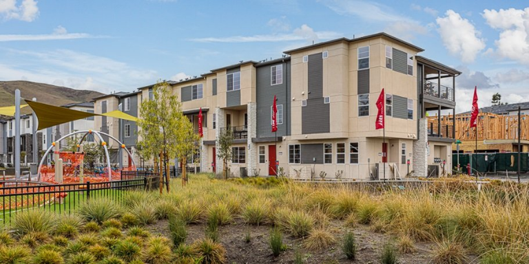 Photo of a grey and white apartment building behind a playground and drought-tolerant plant landscaping.