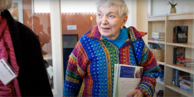 A woman in a colorful sweater holding a folder